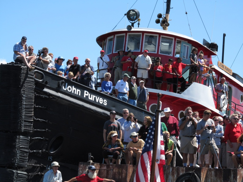 Crowds on the tug watch the races.